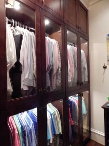 Custom closet with lighting and glass doors.