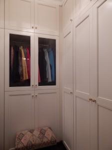 Custom built closet with glass doors.